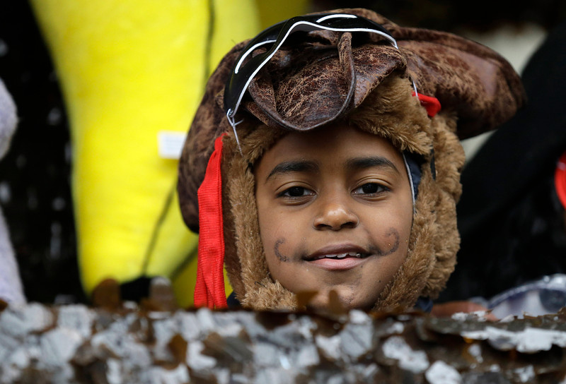 . A child in costume peers from a float in the Krewe of Elks during Mardi Gras in New Orleans, Tuesday, March 4, 2014. Rain and unusually cold temperatures kept most of the normally massive and festive crowds away.  (AP Photo/Gerald Herbert)