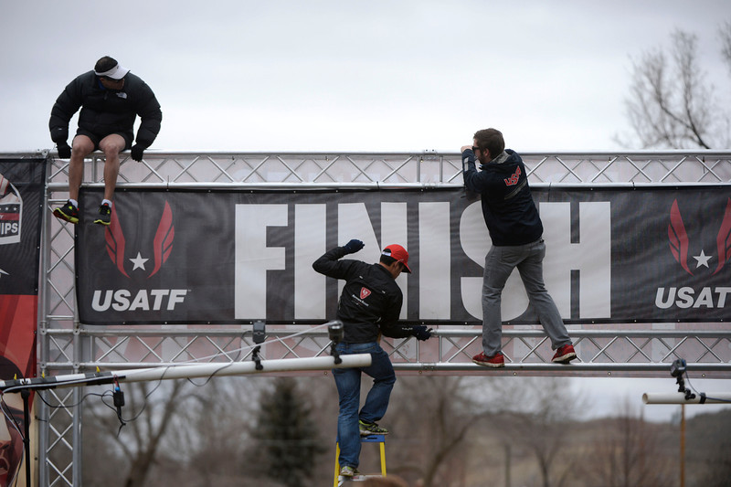 . Workers secure the finish line banner at the  USA Cross Country Championships at the Flatirons Golf Course Saturday afternoon, February 15, 2013. (Photo By Andy Cross / The Denver Post)