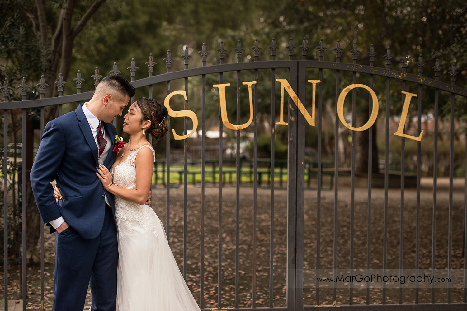 bride and groom with sunol park gate near Casa Bella