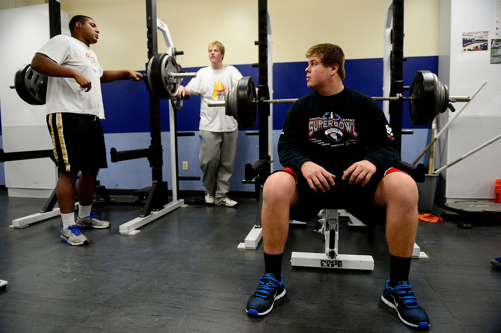 . Valor Christian starting left guard Ryan Cummings prepares to bench press reps of 315 pounds as right tackle Isaiah Holland (left) and left tackle Alec Ruth talk during a lift.  (Photo by AAron Ontiveroz/The Denver Post)
