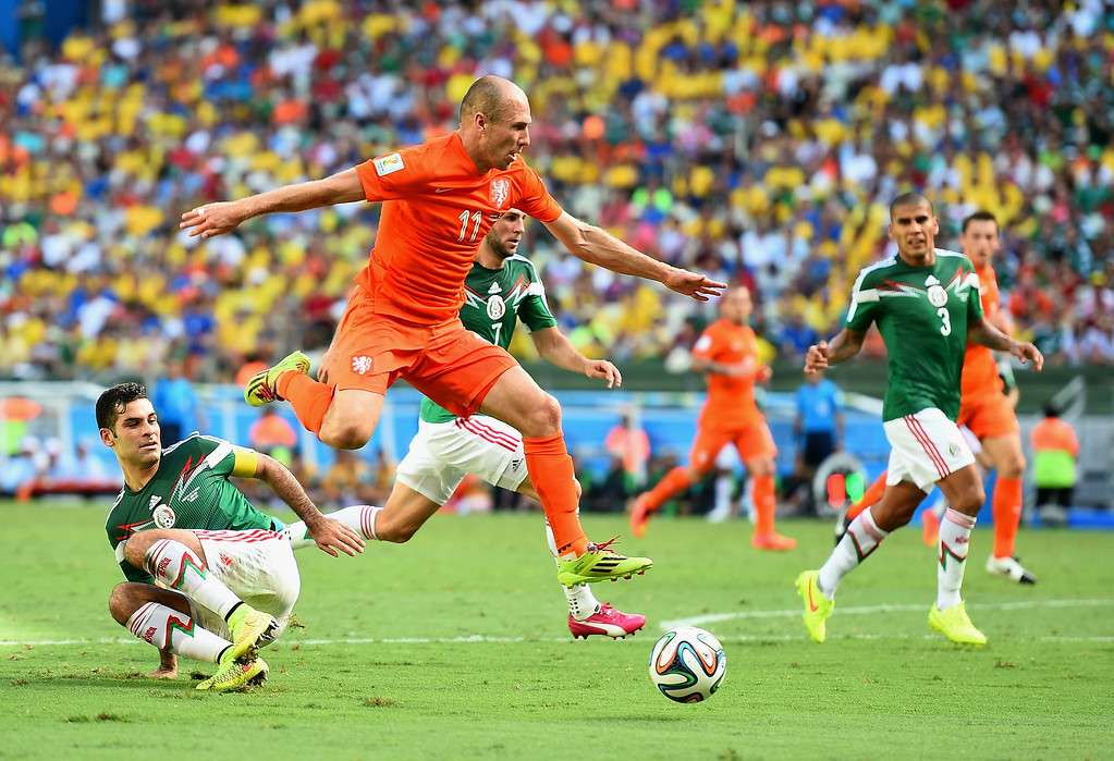 . Arjen Robben of the Netherlands rides the tackle of Rafael Marquez of Mexico during the 2014 FIFA World Cup Brazil Round of 16 match between Netherlands and Mexico at Castelao on June 29, 2014 in Fortaleza, Brazil.  (Photo by Laurence Griffiths/Getty Images)