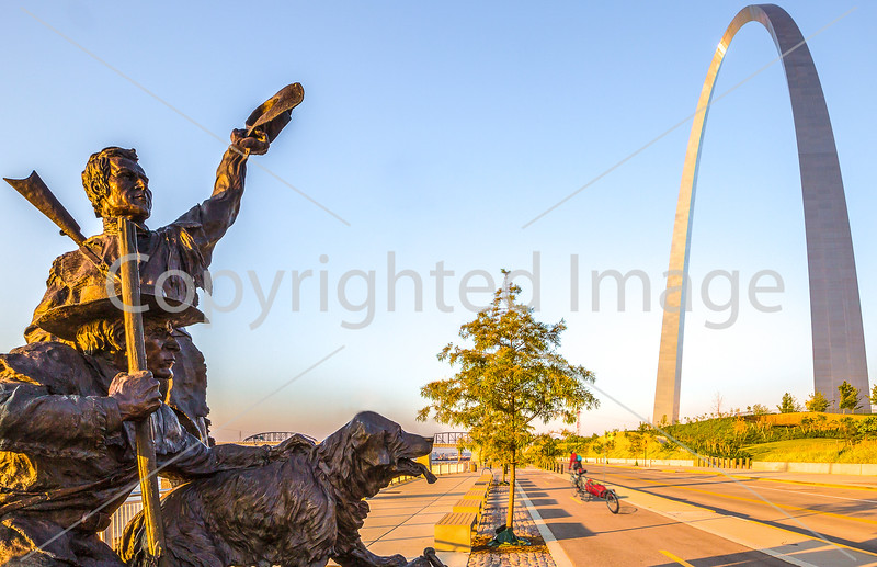 U.S. Bicycle Route 66 - Bike Tourer passes Lewis and Clark Statue on Arch Grounds