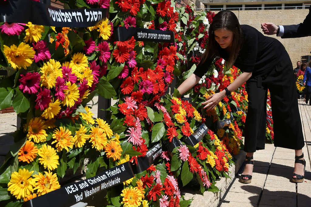 . a woman places a wreath during a ceremony marking the annual Holocaust Remembrance Day at the Yad Vashem Holocaust Memorial in Jerusalem on May 5, 2016. The state of Israel marks the annual Memorial Day commemorating the six million Jews murdered by the Nazis in the Holocaust during World War II. / AFP PHOTO / GALI TIBBON/AFP/Getty Images