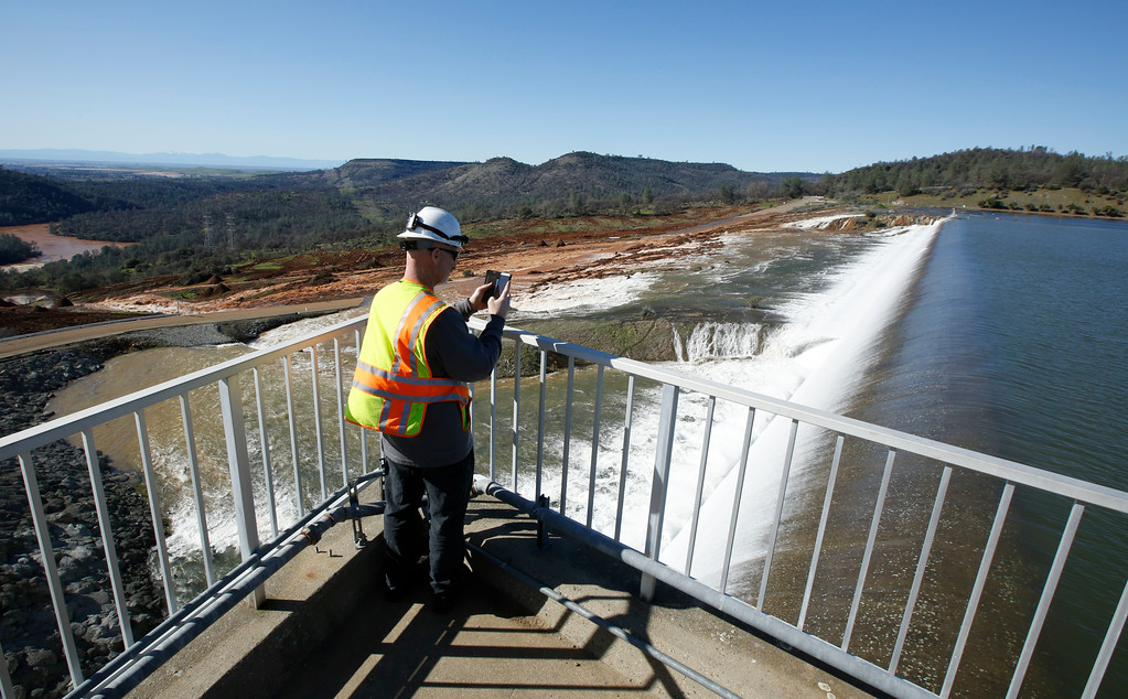 ". In this Saturday, Feb. 11, 2017, photo, Jason Newton, of the Department of Water Resources, takes a picture of water going over the emergency spillway at Oroville Dam in Oroville, Calif. Officials have ordered residents near the Oroville Dam in Northern California to evacuate the area Sunday, Feb. 12, saying a ""hazardous situation is developing\"" after an emergency spillway severely eroded. (AP Photo/Rich Pedroncelli)"