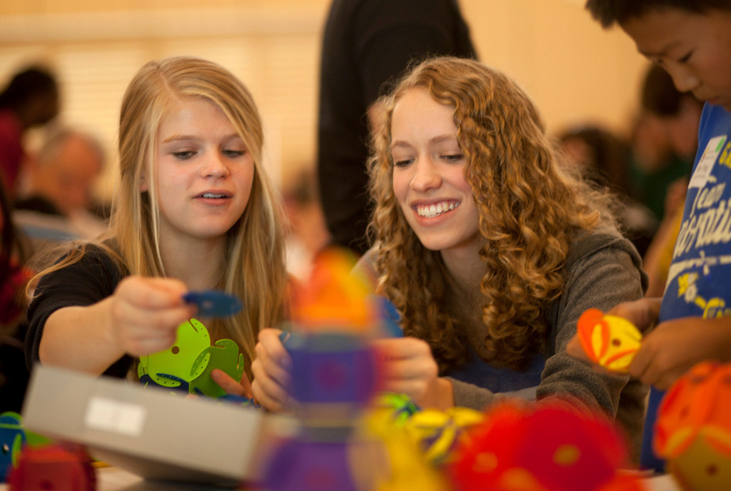 """. Sydney McGillis, 15, left, and Frances Keer, 14, work on a \""""space chips\"""" problem at Stanford University in Stanford Saturday May 11, 2013.  About 350 students in grades 6�12 tested their brainpower and enjoyed a hands-on learning experience covering a wide variety of math topics at the Julia Robinson Mathematics Festival at Stanford. Students circulated among activity tables where teachers, professors, graduate students, and others engaged the youths as they tested their math skills on puzzles, games, and problems.  (Patrick Tehan/Bay Area News Group)"""