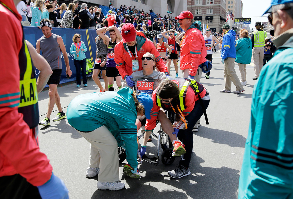 . Rick Barnes Sr., of Clayton, Mo., is helped into a wheelchair after competing in the 120th Boston Marathon on Monday, April 18, 2016, in Boston. (AP Photo/Elise Amendola)