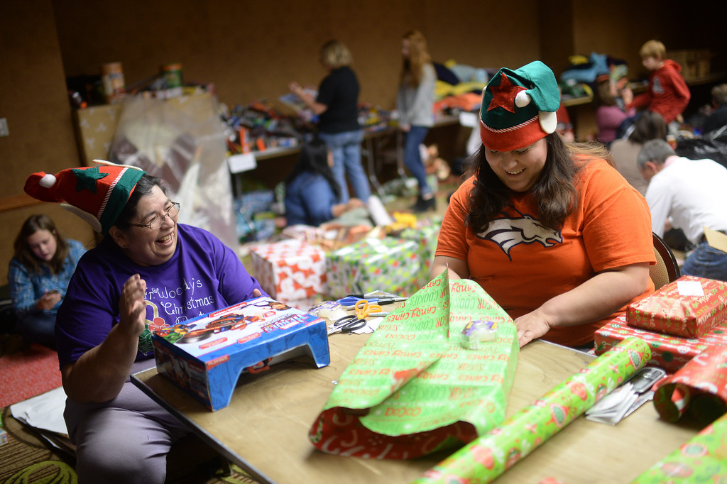 ". DENVER, CO. DECEMBER 21: Barbara Tolmich of Denver, left, and her daughter Leanna are wrapping Christmas gift during the annual Father Woody Christmas Party in Denver, Colorado December 21, 2013. In advance of handing out 5,000 gifts, volunteers are doing a ""wrapping party\"" at the Sheraton Denver Downtown Hotel. (Photo by Hyoung Chang/The Denver Post)"