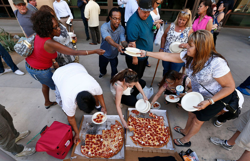 . Several of the dozens of spectators in front of Maricopa County Superior Court building share pizza delivered to the crowd as they wait for a verdict in the Jodi Arias murder trial, Tuesday, May 7, 2013, in Phoenix.  A Phoenix jury is on its third day of deliberations in the trial of Jodi Arias, who is accused of murdering her one-time boyfriend, Travis Alexander, in Arizona. (AP Photo/Ross D. Franklin)