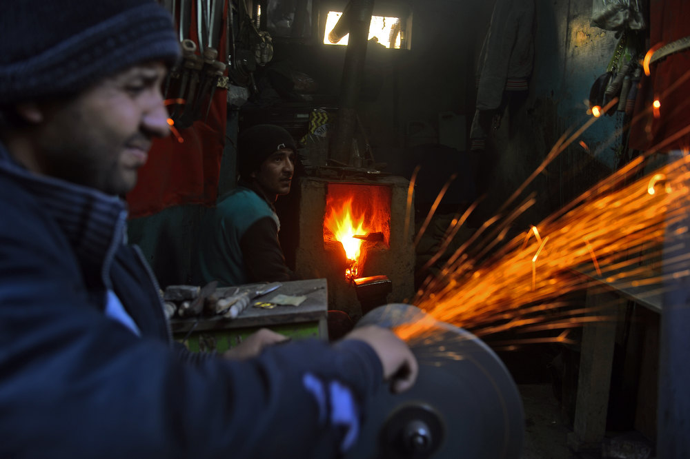 Description of . Afghan workers use a grinder to produce knives at a workshop in the old part of Kabul on December 25, 2012. Over a third of Afghans are living in abject poverty, as those in power are more concerned about addressing their vested interests rather than the basic needs of the population, a UN report said. MASSOUD HOSSAINI/AFP/Getty Images