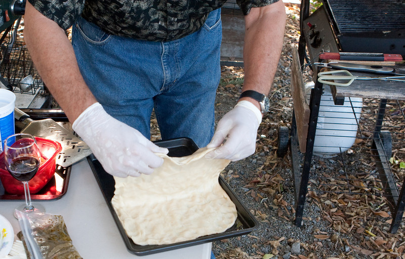 Carefully pick up the pizza dough as a sheet for transfer to the BBQ grill.