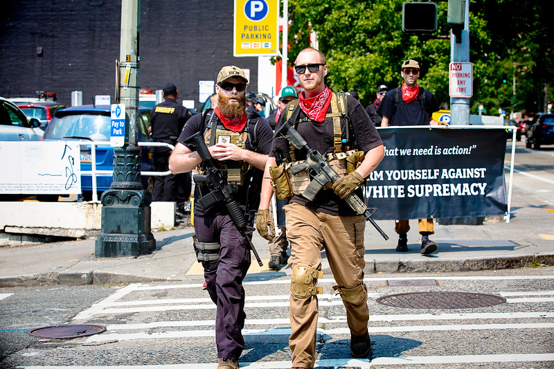 """Heavily armed members of the Puget Sound John Brown Gun Club cross the street to join the counterprotest to the """"Liberty or Death"""" rally in Seattle."""