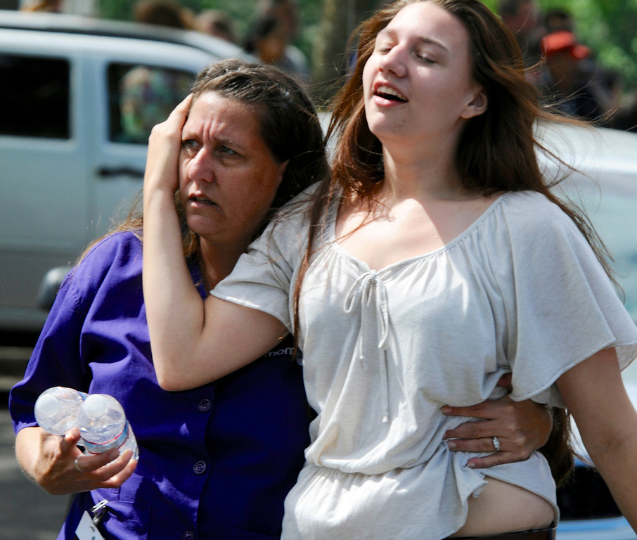 . A family embraces after students arrived at the Fred Meyer grocery store parking lot in Wood Village, Ore., after a shooting at Reynolds High School Tuesday, June 10, 2014, in nearby Troutdale.  (AP Photo/Greg Wahl-Stephens)