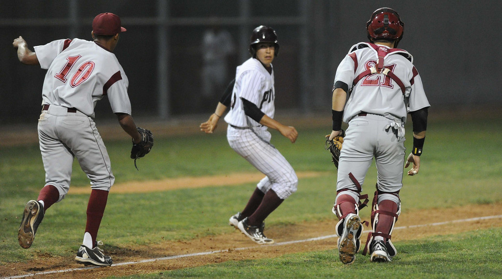 . 03-21-2013--(LANG Staff Photo by Sean Hiller)- Paramount hosts Downey in Thursday\'s high school baseball game. Paramount\'s Frankie Valenzuela tries to out run Downey\'s catcher Juan Gonzalez, right, before finally getting tagged out by Downey\'s pitcher Richard Gomez (10).