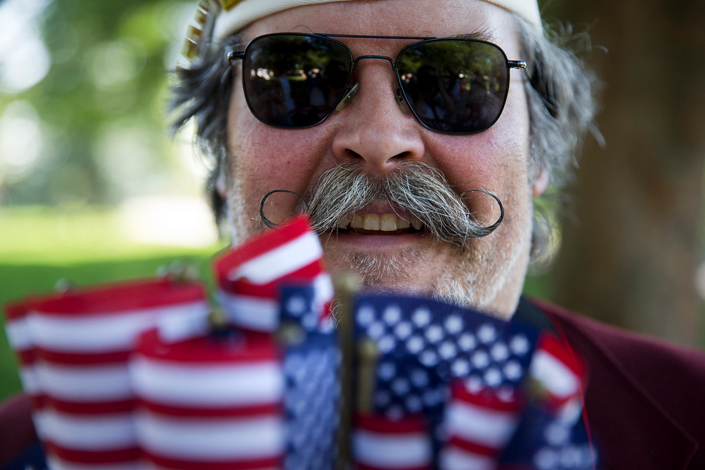 . Navy veteran Mike Bukowski, of Virginia Beach, Va., hands out small U.S. flags at Arlington National Cemetery in Arlington, Va., for Memorial Day Monday, May 26, 2014. (AP Photo/Jacquelyn Martin)