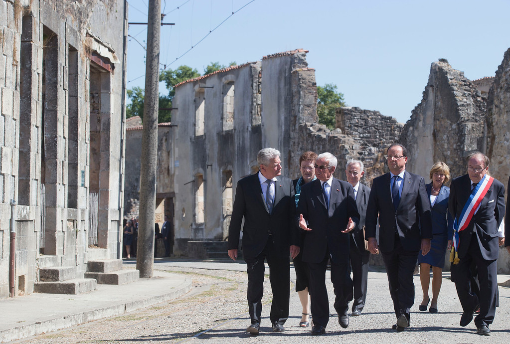 . From left,  German President Joachim Gauck, Robert Hebras, one of the two survivors still alive, French President Francois Hollande and Mayor of Oradour-sur Glane, Raymond Fugier walk through the ghost city of Oradour-sur-Glane, southwestern France, Wednesday, Sept. 4, 2013, where on June 10, 1944, the Nazis massacred 642 civilians. Holding hands in quiet tribute, the presidents of Germany and France are visiting the scene of the largest massacre in Nazi-occupied France nearly seven decades ago. Wednesday\'s visit by German President Joachim Gauck to the southwestern French town of Oradour-sur-Glane is the first by a serving German leader. (AP Photo/Michel Euler, Pool)