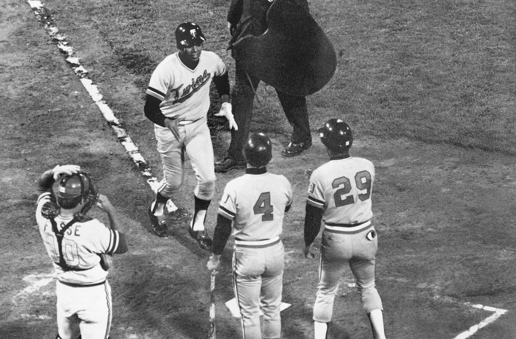 . Minnesota Twins designated hitter Tony Oliva approaches home plate after hitting major league baseball\'s first designated hitter homerun at Oakland Coliseum in Oakland on April 6, 1973. Oliva hit the first pitch from Oakland starter Jim Hunter to right field. Greeting him are Twins players Steve Braun (4) and Rod Carew (29). (AP Photo)