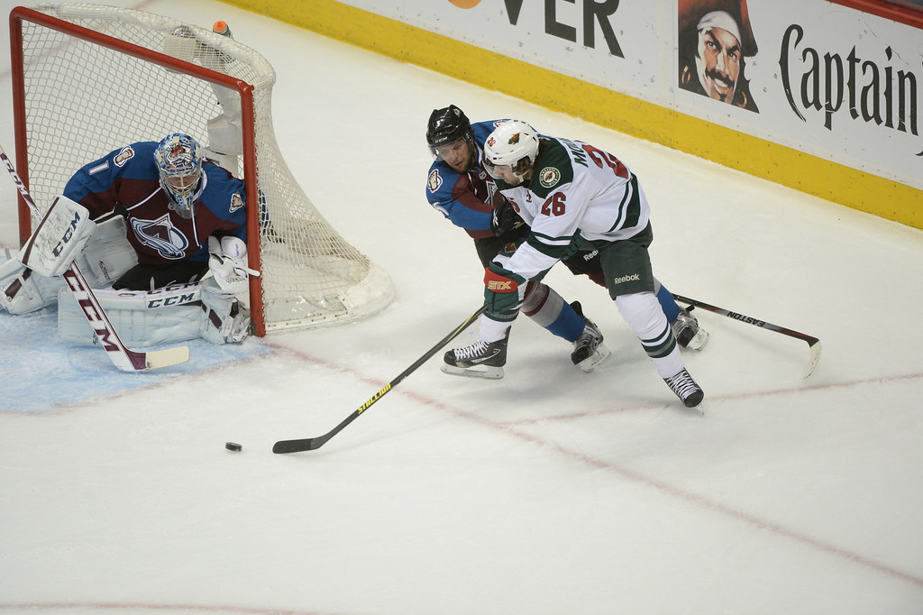 . Nate Guenin (5) of the Colorado Avalanche defends against Matt Moulson (26) of the Minnesota Wild in front of Avalanche goaltender Semyon Varlamov (1) during the first period of action.  (Photo by Karl Gehring/The Denver Post)