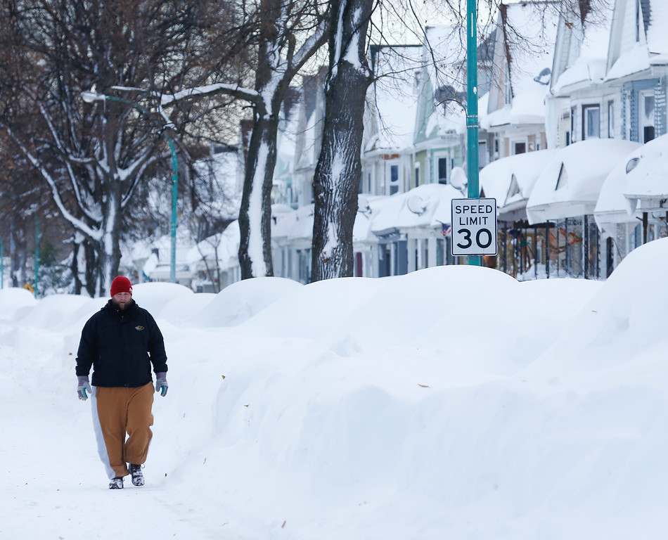 . Chris Weiglein walks along his snow-bound south Buffalo neighborhood on Thursday, Nov. 20, 2014, in Buffalo, N.Y. A new blast of lake-effect snow pounded Buffalo for a third day piling more misery on a city already buried by an epic, deadly snowfall that could leave some areas with nearly 8 feet of snow on the ground when it\'s all done. (AP Photo/Mike Groll)