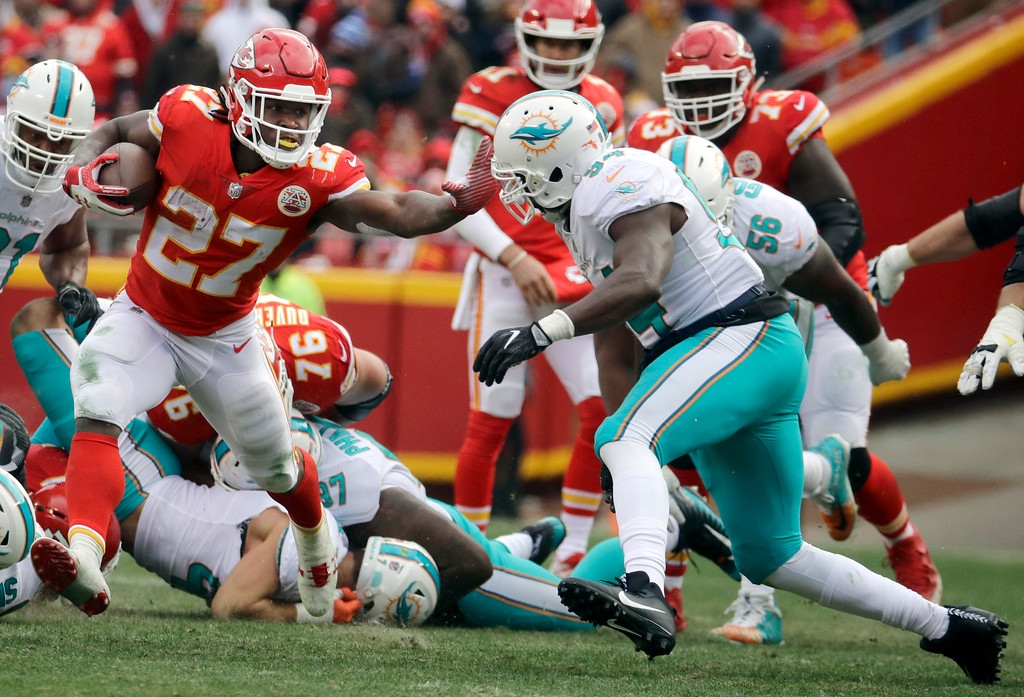 . Kansas City Chiefs running back Kareem Hunt (27) stiff-arms Miami Dolphins linebacker Lawrence Timmons (94) during the first half of an NFL football game in Kansas City, Mo., Sunday, Dec. 24, 2017. (AP Photo/Charlie Riedel)