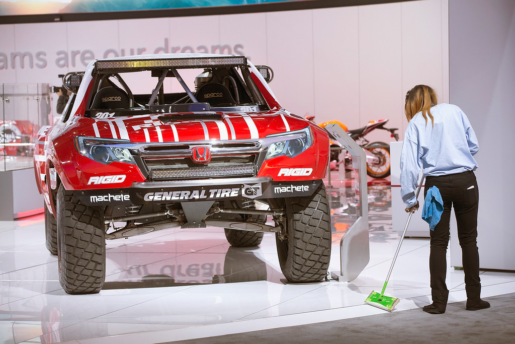 . A worker cleans up around a Honda Ridgeline race truck on display at the North American International Auto Show on January 12, 2016 in Detroit, Michigan. The show is open to the public from January 16-24.  (Photo by Scott Olson/Getty Images)
