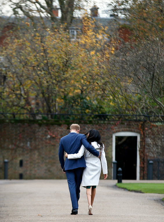 . Britain\'s Prince Harry and Meghan Markle walk away after posing for the media in the grounds of Kensington Palace in London, Monday Nov. 27, 2017. It was announced Monday that Prince Harry, fifth in line for the British throne, will marry American actress Meghan Markle in the spring, confirming months of rumors. (AP Photo/Alastair Grant)