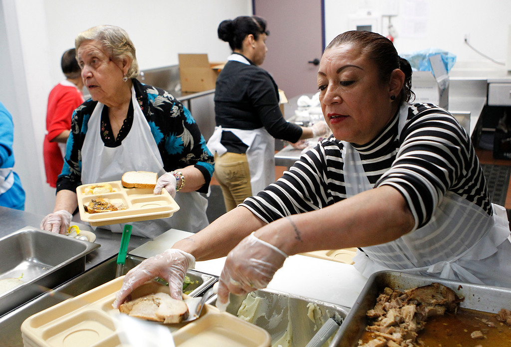 . At right, the cook, Maria Lopez, dishes out pork loins as volunteer Rosario Gonzales, left, helps with other food during a county subsidized lunch at the Eastside Neighborhood Center of the Catholic Charities of Santa Clara County in San Jose, Calif. on Wednesday, Feb. 27, 2013. (LiPo Ching/Staff)