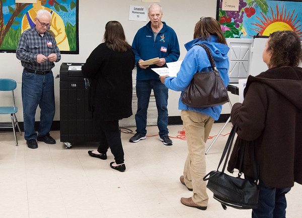 11/06/18 Wesley Bunnell | Staff Tabulation Tenders Gus Prisco, L, and Carl Symecko help voters to enter their ballots into the tabulation machine at the Pulaski Middle School polling location on Tuesday afternoon.