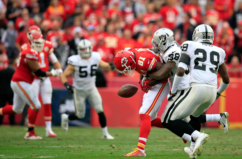. KANSAS CITY, MO - DECEMBER 14:   T.J. Carrie #38 of the Oakland Raiders breaks up a pass intended for  Jason Avant #81 of the Kansas City Chiefs during the second quarter at Arrowhead Stadium on December 14, 2014 in Kansas City, Missouri.  (Photo by Jamie Squire/Getty Images)