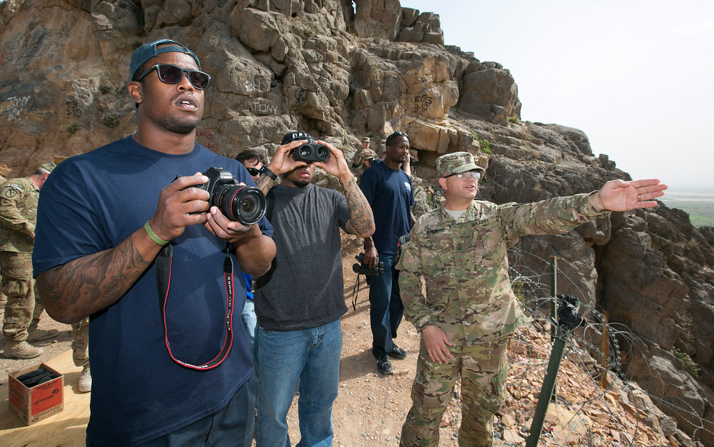 . Cleveland Browns linebacker D�Qwell Jackson (l), Carolina Panthers wide receiver Steve Smith (2nd l), and Denver Broncos cornerback Champ Bailey (3rd l) look out from a mountaintop in the Middle East during a tour given by a U.S. soldier during a USO/NFL tour stop on March 18, 2013. USO Photo by Fred Greaves