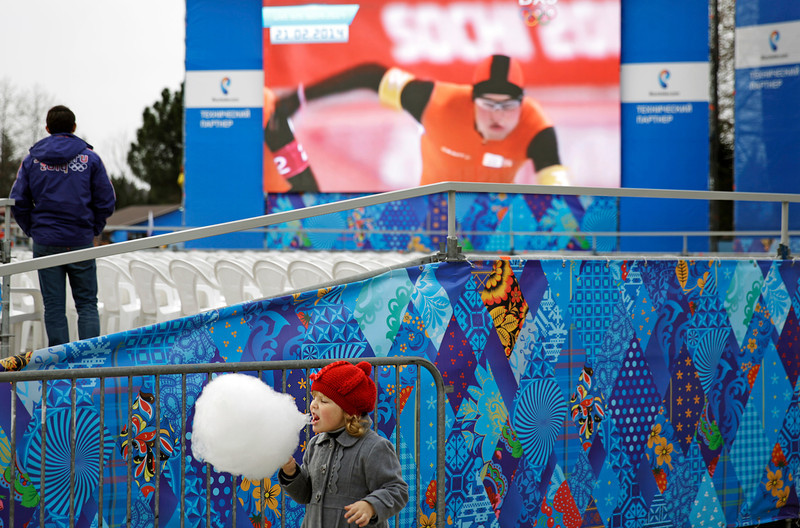 . A girl walks by with cotton candy as a big screen shows a broadcast of the speed skating competition from the nearby 2014 Winter Olympics at an amusement park, Saturday, Feb. 22, 2014, in Adler, Russia. (AP Photo/David Goldman)