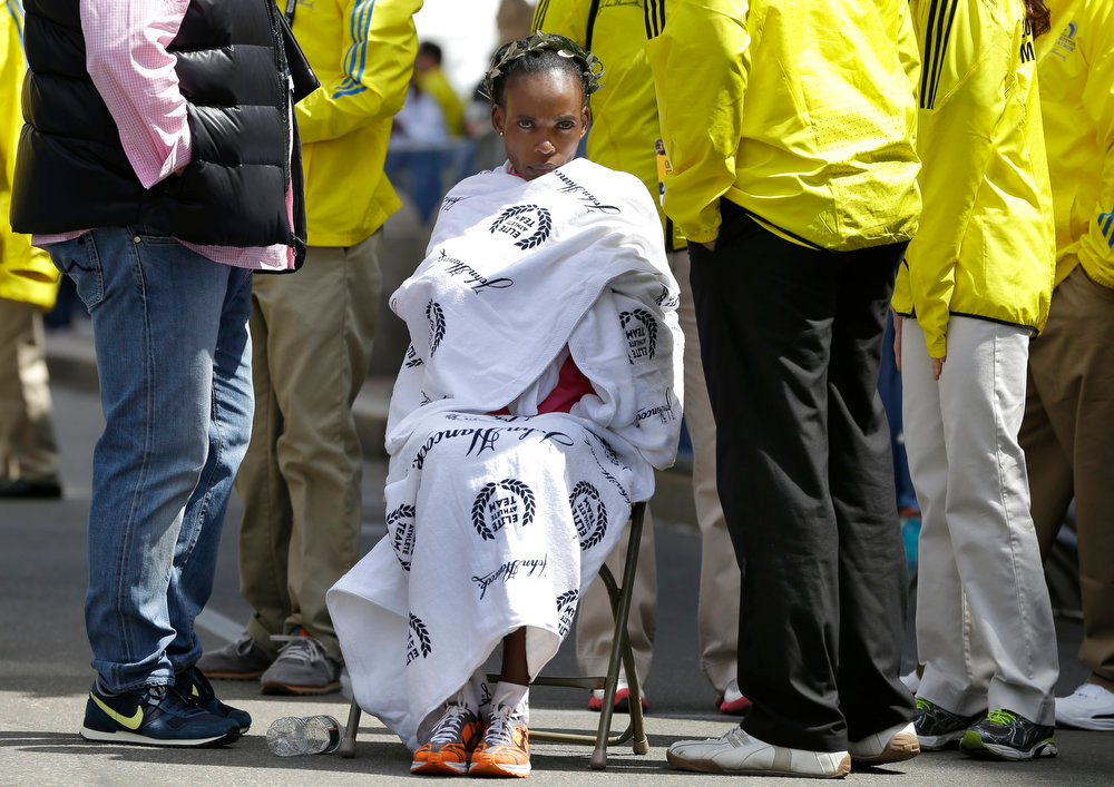 . Rita Jeptoo of Kenya sits wrapped in a towel as she rests in the finish area after winning the women\'s division of the 2013 Boston Marathon in Boston Monday, April 15, 2013. (AP Photo/Elise Amendola)