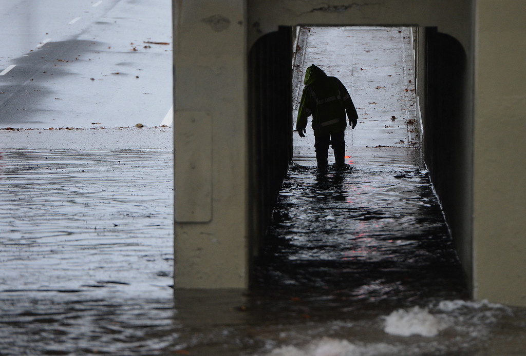 . A person slogs through the flooded Caltrain underpass on Santa Clara Street near the SAP Center in San Jose, Calif., on Thursday, Dec. 11, 2014. The big storm made its way south, after pounding the North Bay in the early morning hours. (Dan Honda/Bay Area News Group)