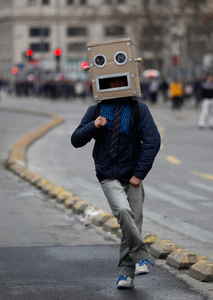 Description of . A demonstrator, wearing a mask, dances during a national strike in Santiago, Chile, Wednesday, Aug. 24, 2011. Some people are stoning buses and burning barricades as Santiago's streets fill with tear gas. Protesters planned marches downtown, but the government has warned them to stay out, threatening to invoke Chile's severe state security law against people who