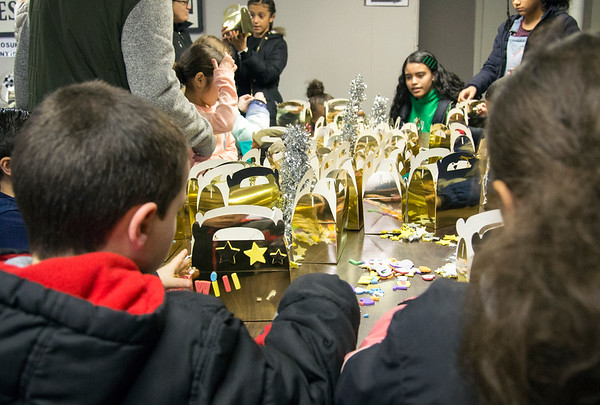 01/06/19 Wesley Bunnell | Staff Three Kings Day was celebrated at Neighborhood Services of New Britain at 223 Broad St for families on Monday night. Wilfredo Irizarry, L age 6, and Taliyah Homar, R age 10< work on decorating their gold gift baskets.