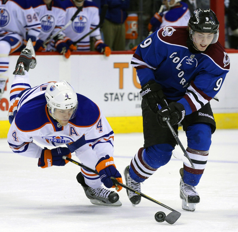 . Edmonton Oilers left wing Taylor Hall (4) lunges for the puck against Colorado Avalanche center Matt Duchene (9) in the second period of an NHL hockey game on Friday, April 19, 2013, in Denver. (AP Photo/Joe Mahoney)