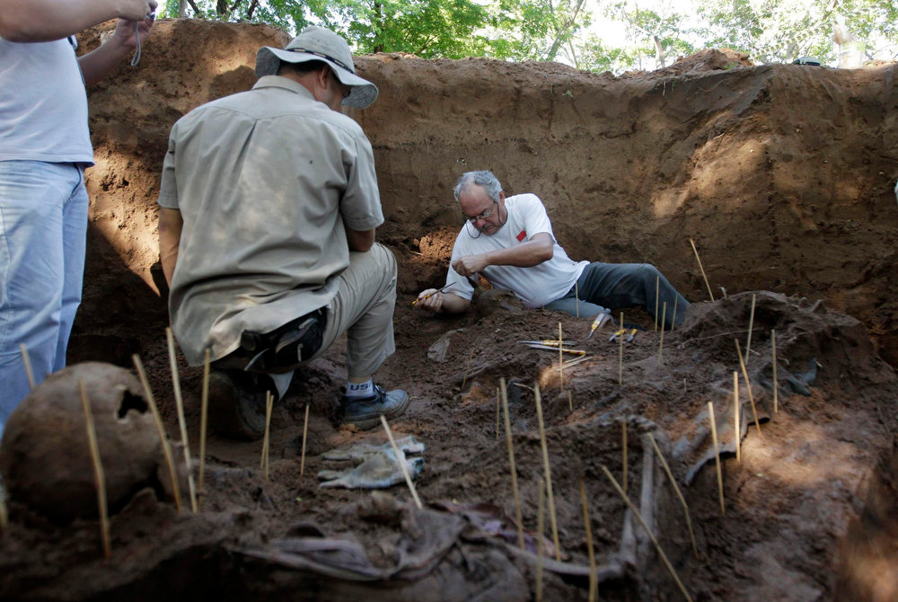 Description of . Argentine forensic expert Rogelio Agustin Goiburu (R) excavates human remains discovered in the grounds of a police barracks in Asuncion, Paraguay on March 21, 2013. According to the researchers, 15 more skeleton remains, likely to be victims of the 1954 to 1989 dictatorship under Alfredo Stroessner, were found in the last two days. Goiburu\'s father, Augustin Goiburu, was arrested in Argentina during the Dirty War and brought to Paraguay where he disappeared and was presumed killed. REUTERS/Jorge Adorno