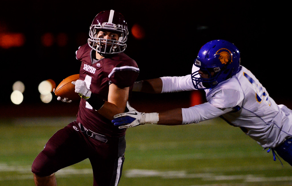 . Erica Miller - The Saratogian @togianphotog      Burnt Hills-Ballston Lake\'s Daniel Porter carried the ball down the field against Queensbury\'s Jeffery Underhill for the Section 2 Class A Superbowl Saturday evening Nov. 9, 2013.SAR-l-footballs1