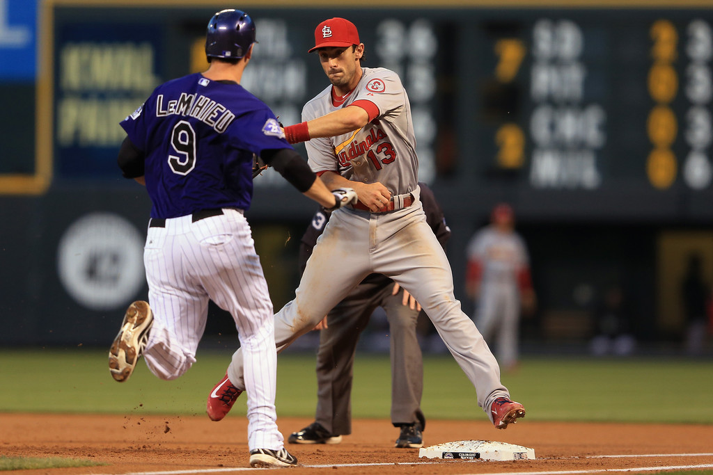 . Second baseman Matt Carpenter #13 of the St. Louis Cardinals gets a put out on DJ LeMahieu #9 of the Colorado Rockies at first base in the first inning at Coors Field on September 16, 2013 in Denver, Colorado.  (Photo by Doug Pensinger/Getty Images)
