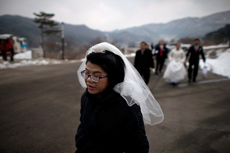 ". A bride arrives for a mass wedding at an event held by the Unification Church in Gapyeong on February 12, 2014. Unification Church members forming 2500 couples from 52 countries were married in a mass wedding in South Korea -- only the second such event since the death of their ""messiah\"" and controversial church founder Sun Myung Moon. (ED JONES/AFP/Getty Images)"