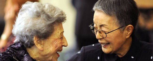 . Myrtle Feenberg and Akiko Collins share a smile while sitting down for a traditional Passover Seder at the Los Angeles Jewish Home in Reseda on March 20, 2013.(Andy Holzman/Los Angeles Daily News)