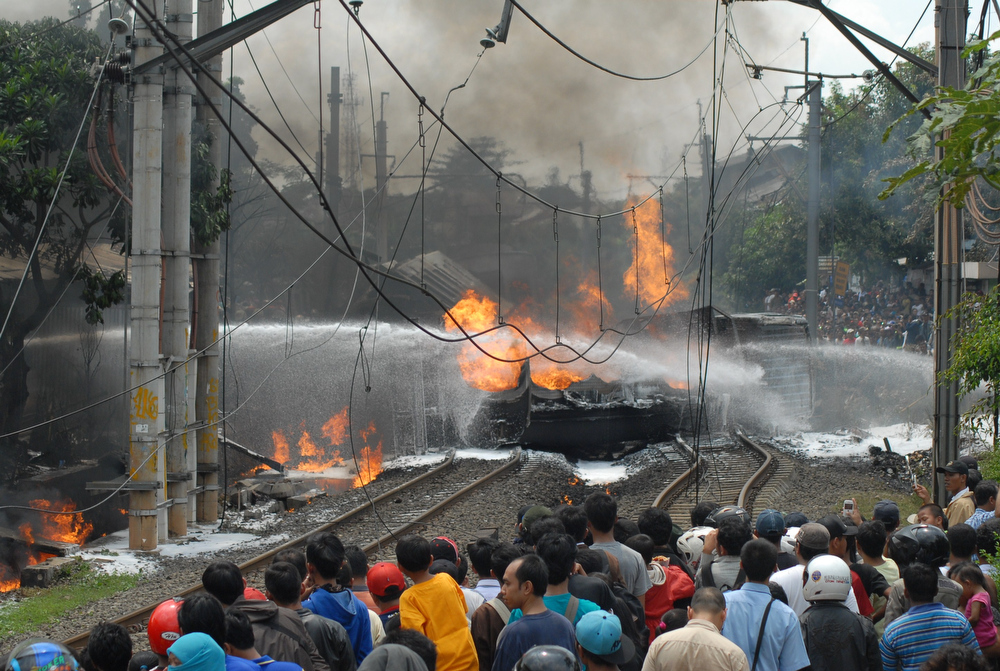 . People look on as a fire is extinguished following a collision between a commuter train and fuel truck at Bintaro, western Jakarta, on December 9, 2013. At least four people were killed when a commuter train collided with a fuel truck near the Indonesian capital Jakarta on December 9, derailing a women-only carriage which burst into flames, officials said.  BIMA SAKTI/AFP/Getty Images