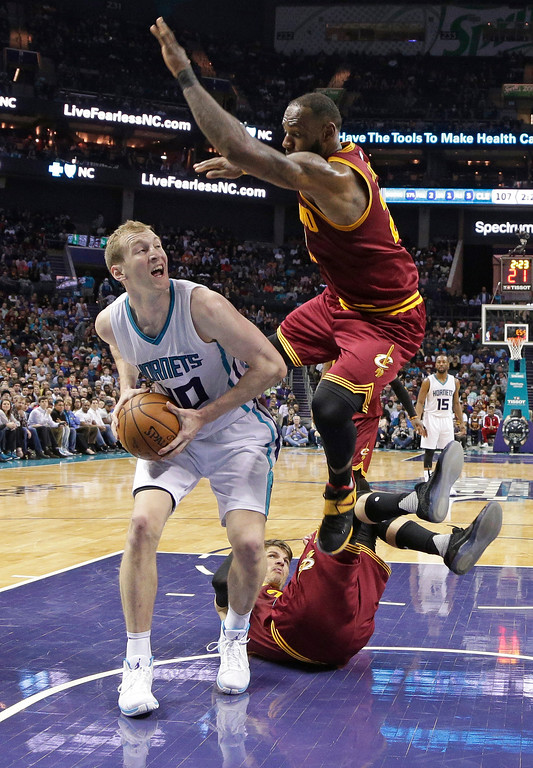 . Cleveland Cavaliers\' LeBron James, right, jumps over teammate Kyle Korver to defend against Charlotte Hornets\' Cody Zeller, left, during the second half of an NBA basketball game in Charlotte, N.C., Friday, March 24, 2017. The Cavaliers won 112-105. (AP Photo/Chuck Burton)