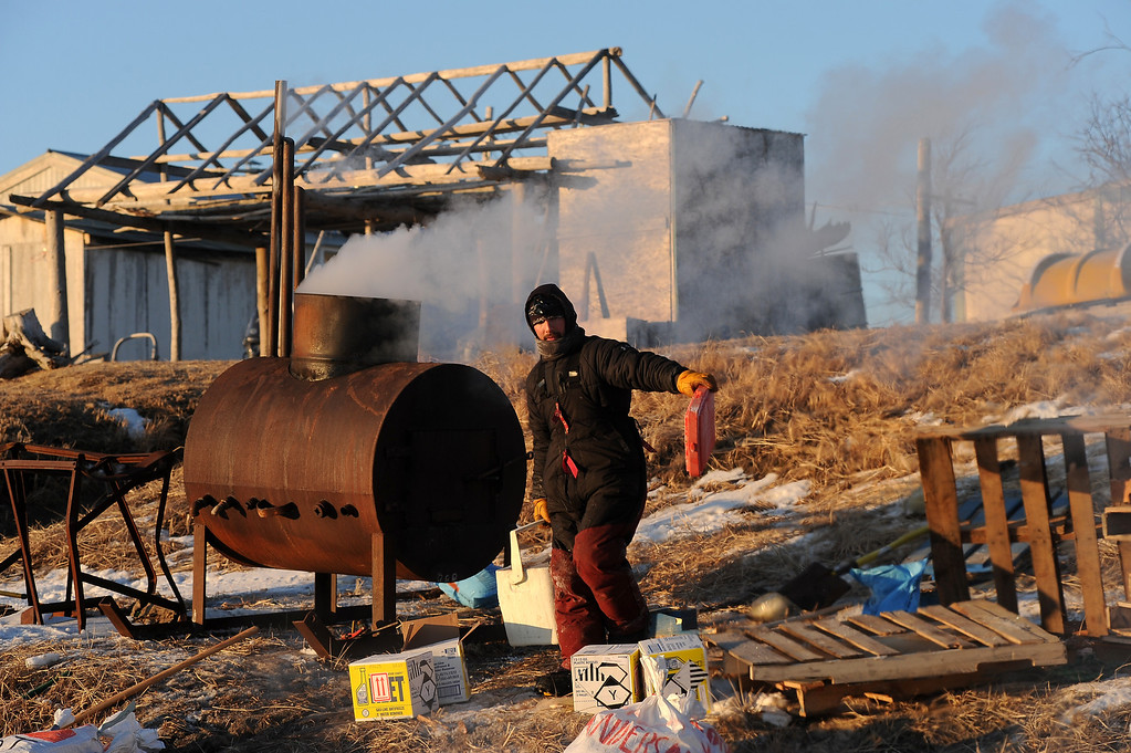. Iditarod musher Richie Diehl, from Aniak, AK, gets hot water to prepare dog food for his team at the Unalakleet checkpoint at sunrise during the 2014 Iditarod Trail Sled Dog Race on Sunday, March 9, 2014. (AP Photo/The Anchorage Daily News, Bob Hallinen)
