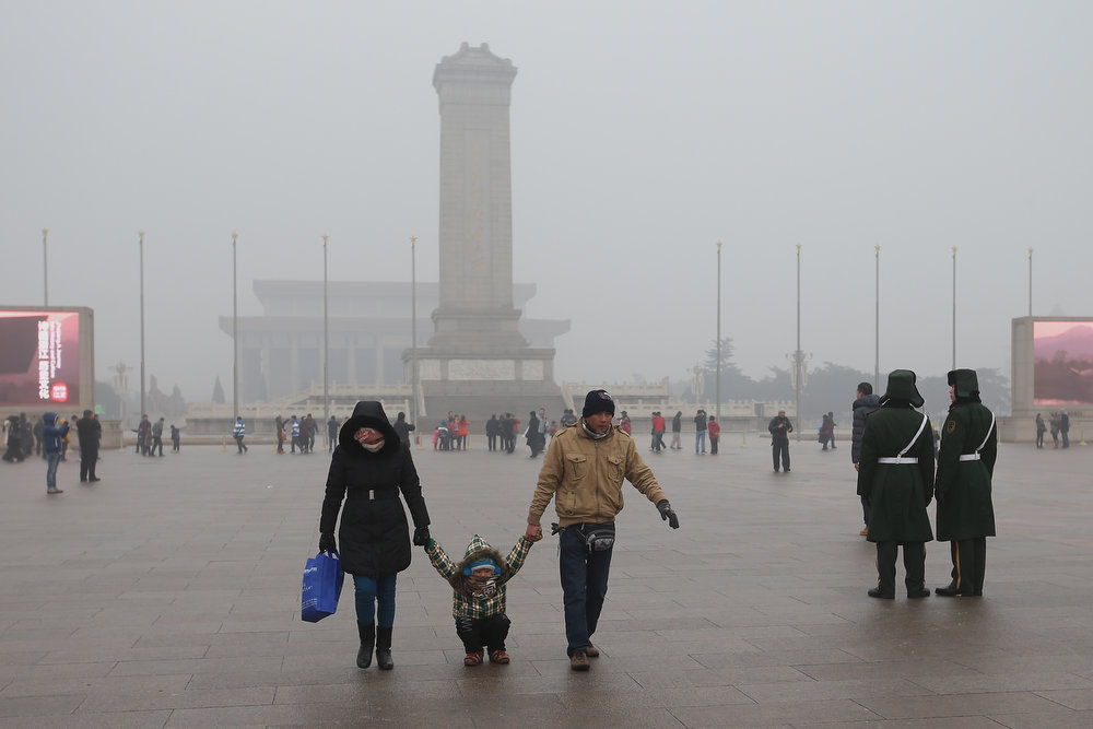 . A little tourist and his parents play on the ground with frozen ice at the Tiananmen Square during severe pollution on January 31, 2013 in Beijing, China. Heavy smog that has choked Beijing for the last five days weakened slightly on Thursday due to a light rainfall, although the capital\'s air remains heavily polluted. The haze choking many Chinese cities covers a total area of 1.43 million square kilometers, the China\'s Ministry of Environmental Protection said Wednesday.  (Photo by Feng Li/Getty Images)