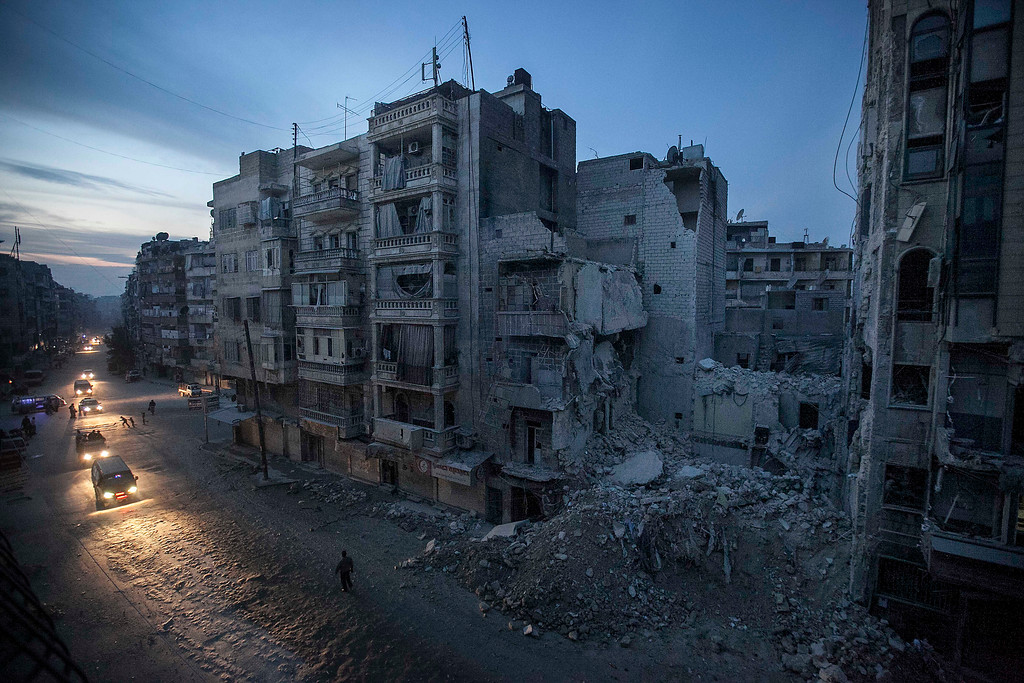 . In this Thursday, Nov. 29, 2012 file photo, night falls on a Syrian rebel-controlled area as destroyed buildings, including Dar Al-Shifa hospital, are seen on Sa\'ar street after airstrikes targeted the area last week, killing dozens in Aleppo, Syria. More than two years into Syria\'s civil war, the once highly-centralized authoritarian state has effectively split into three distinct parts, each boasting its own flags, security agencies and judicial system. (AP Photo/Narciso Contreras)
