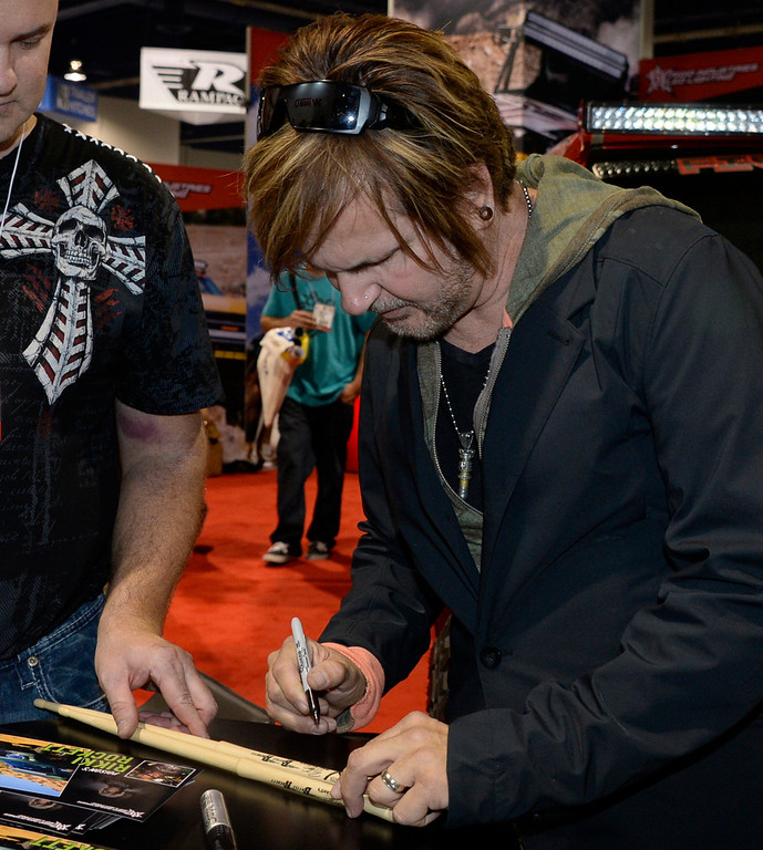 . Nov 6,2013 Las Vegas NV. USA. 1980s Poison drummer Rikki Rocket signs autographs at the Rigid LED lighting booth during the second day of the 2013 SEMA auto show. Photo by Gene Blevins/LA Daily News