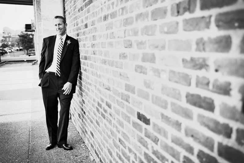 groom against brick wall
