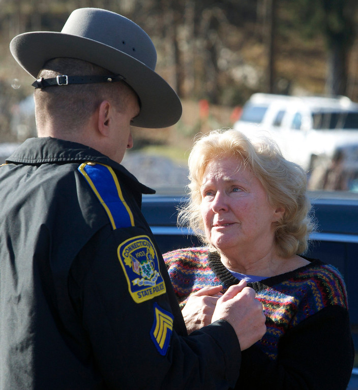 . A woman speaks with a Connecticut State Trooper outside Sandy Hook Elementary School after a shooting in Newtown, Connecticut, December 14, 2012. A shooter opened fire at the elementary school in Newtown, Connecticut, on Friday, killing several people including children, the Hartford Courant newspaper reported.  REUTERS/Michelle McLoughlin