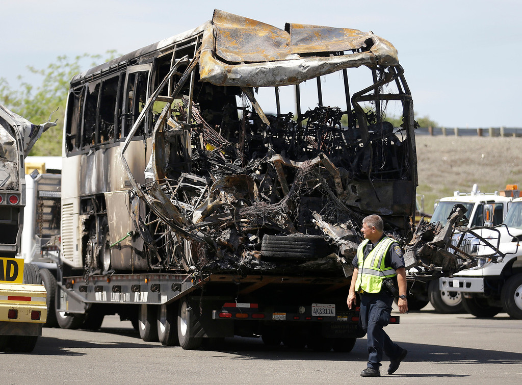 . A California Highway Patrol officer walks past the charred remains of a tour bus at a CalTrans maintenance station in Willows, Calif., Friday, April 11, 2014. At least ten people were killed and dozens injured in the fiery crash on Thursday, April 10, between a FedEx truck and a bus carrying high school students on a visit to a Northern California college. (AP Photo/Jeff Chiu)