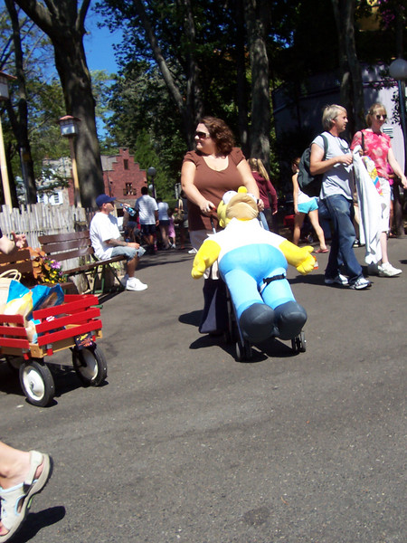 Pushing a giant Homer Simpson plush doll in a stroller.